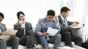 Business people sitting on a sofa waiting in office