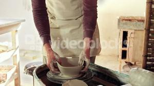 Mid section of potter making pot