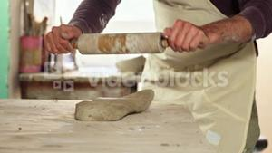 Male potter molding clay with rolling pin