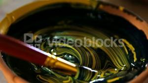 Potter mixing paint into bowl