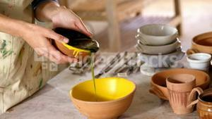 Mid-section of female potter pouring paint into bowl