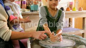 Mother assisting her daughter in making a bowl