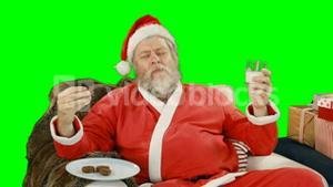 Santa claus relaxing on couch and having sweet food