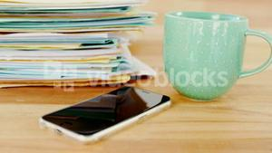 Coffee mug, mobile phone and stacked files on table