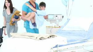 Doctor helping a child into bed