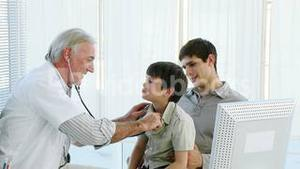 Senior doctor listening to a child with a stethoscope