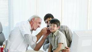 Doctor examining little boys ears in office