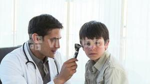 Doctor examining kids ears in office