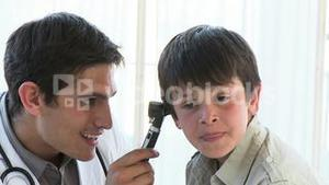 Close up of doctor examining little boys ears