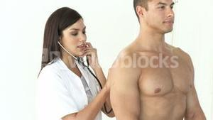 Female doctor listening with a stethoscope to patient