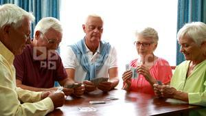 Senior friends playing cards in living room