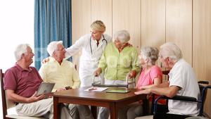 Female doctor interacting with senior citizens