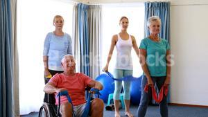 Trainer assisting senior citizens in performing stretching exercise
