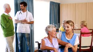 Doctor and nurse interacting with senior citizens
