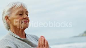 Senior woman meditating on beach