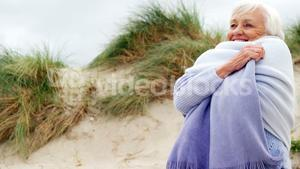 Happy senior woman in sweater feeling cold