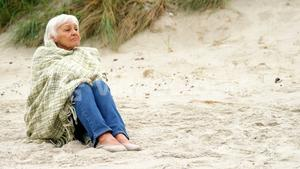 Thoughtful retired woman sitting on the beach