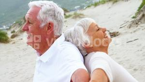 Senior couple standing back to back with arms outstretched