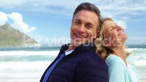 Mature couple standing back to back on beach