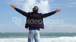 Mature man standing with arms outstretched on the beach