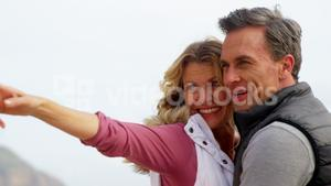 Happy mature couple pointing at view