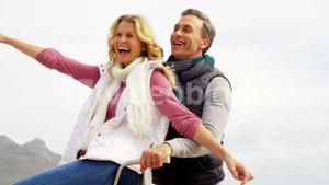 Happy mature couple sitting on bicycle with arms outstretched