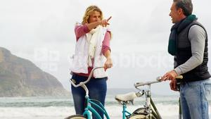 Couple standing with their bicycle