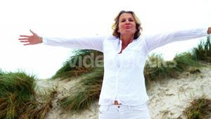 Mature woman with arms outstretched at beach