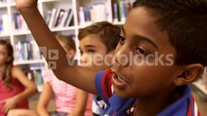 Schoolboy raising hand in library