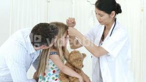 Panorama of doctor taking little girls temperature