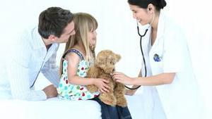 Doctor listening to a teddy bear with a stethoscope