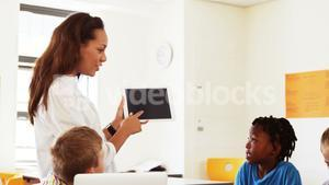 Teacher teaching school kids on digital tablet in classroom