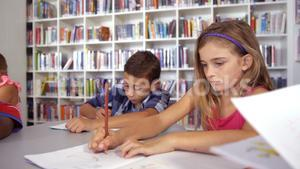 School kids drawing in book in classroom