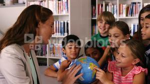 Teacher assisting school kids in reading globe in library