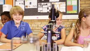 School kids looking through microscope in laboratory