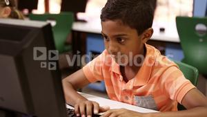 Schoolboy studying on personal computer in classroom