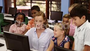 Teacher assisting school kids on personal computer in classroom