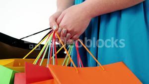 Woman holding shopping bag against white background