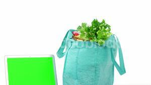 Fresh vegetables in shopping bag with laptop