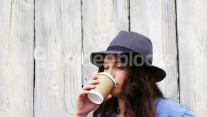 Beautiful woman in hat having coffee