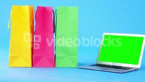 Multicolored shopping bags and laptop on blue background