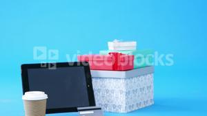 Credit card, gift box, disposable coffee cup and digital tablet on blue background