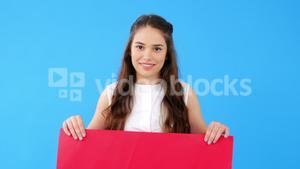 Beautiful woman holding blank placard on blue background