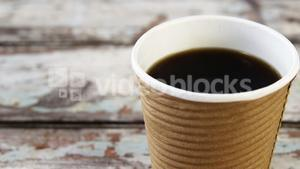 Disposable coffee cup on wooden plank