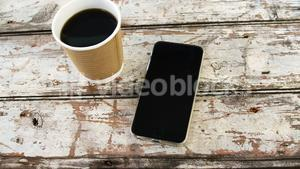 Disposable coffee cup and mobile phone on wooden plank