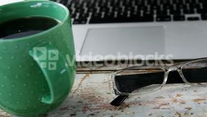 Coffee mug, laptop, spectacle on wooden plank