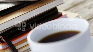 Stack of books, coffee cup, mobile phone on wooden plank