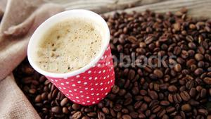 Disposable cup with coffee beans on wooden plank