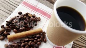 Disposable cup with coffee beans and cinnamon on wooden plank