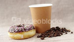 Disposable coffee cup and chocolate doughnut and coffee bean with sprinkles